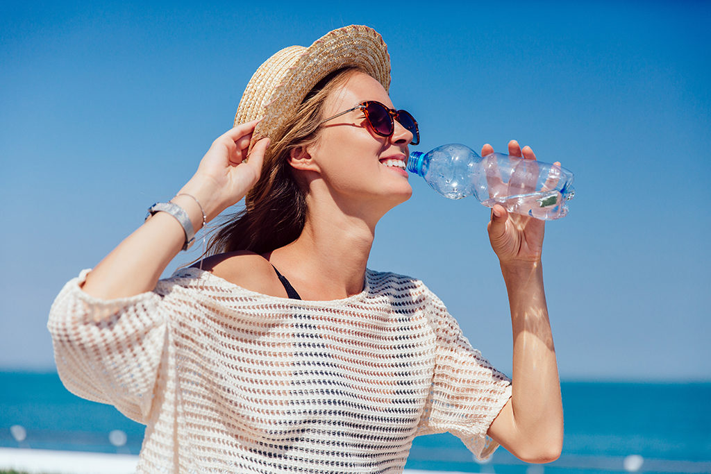 happy-pretty-girl-sunglasses-drinking-clear-water-during-walking-quay